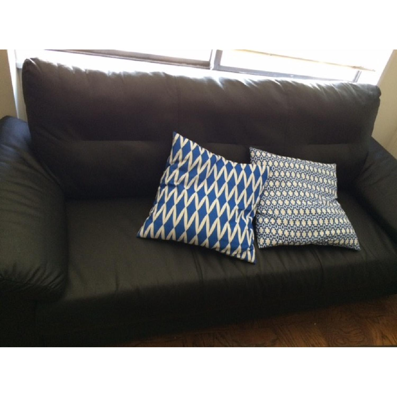 Picture of: Black Leather Couch W 2 Blue Pillows Aptdeco