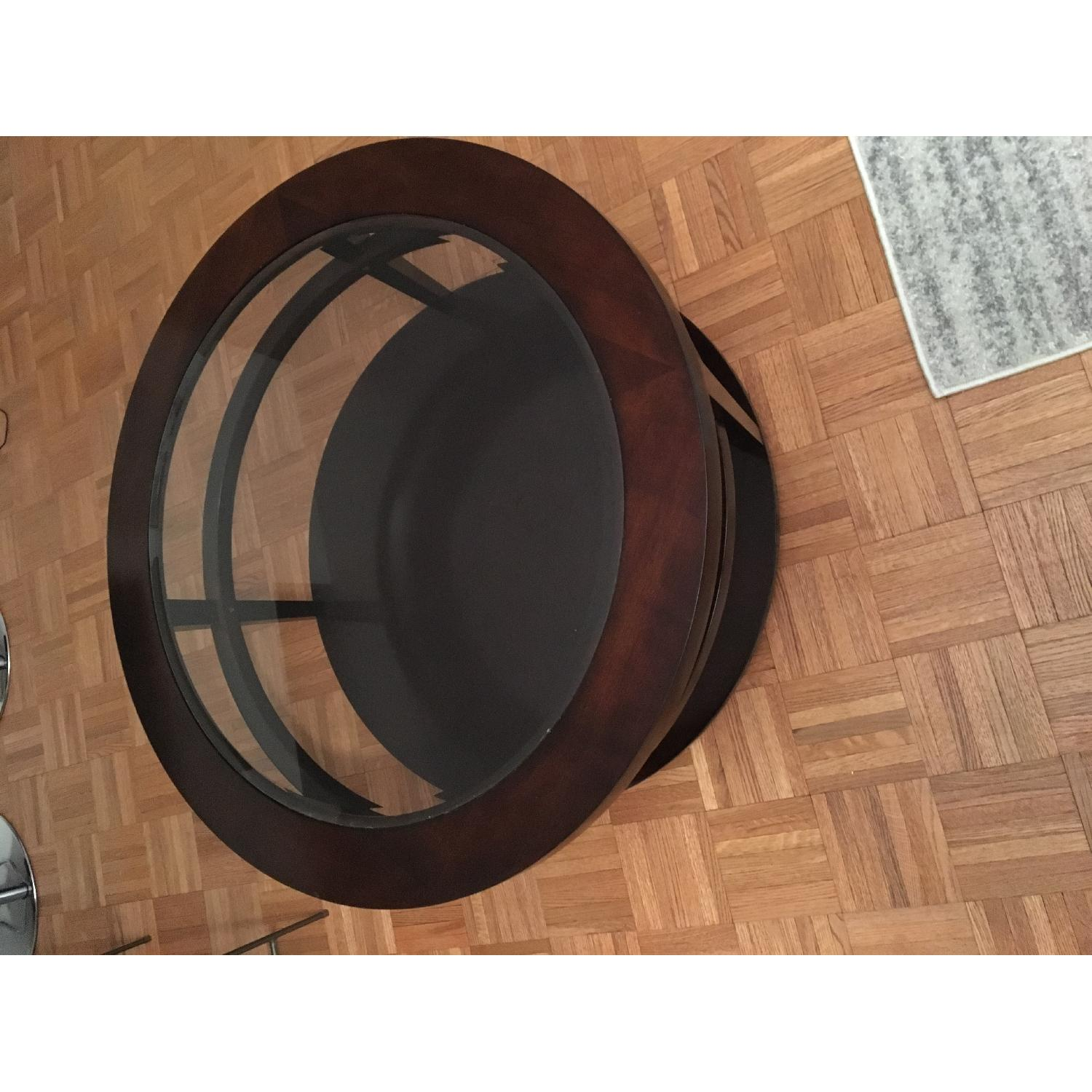 Macy's Round Wood/Glass Coffee Table on Casters - image-1