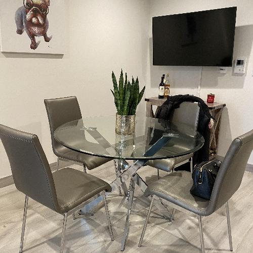 Used kitchen table set, glass top, silver leather chairs for sale on AptDeco